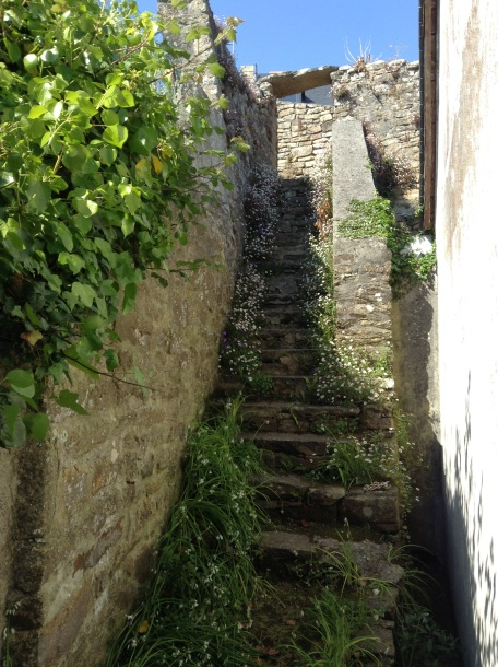 1) Stone steps at the side of the cottage rise steeply up to join the ancient walled pathways that lead up to the town